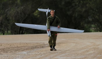 An Israeli soldier carries a drone near the Israel and Gaza border on Thursday, March 13, 2014