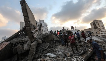 People inspect the rubble of a building following an Israeli airstrike on Gaza City, August 9, 2018.