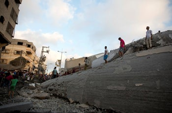 Palestinians inspect a damaged building after it was hit by an Israeli airstrike, Gaza City, August 9, 2018.