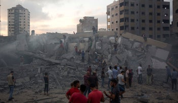 Palestinians inspect a damaged building after an Israeli airstrike in Gaza City, Thursday, August 9, 2018