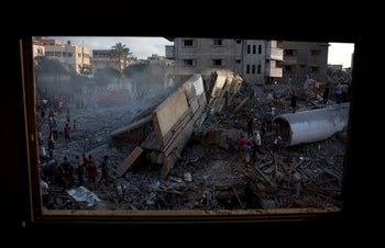 Palestinians inspect the damaged building of Said al-Mis'hal cultural center after an Israeli airstrike in Gaza City, Thursday, August 9, 2018
