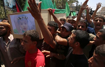 Palestinian mourners chant Islamic slogans while carrying the coffin of a 23-year-old pregnant mother and her daughter during their funeral in Deir el-Balah, Gaza Strip, August 9, 2018