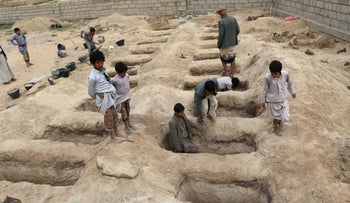 Boys inspect graves prepared for victims of Thursday's air strike in Saada province, Yemen August 10, 2018