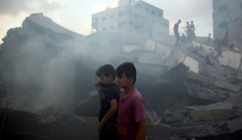 Palestinians inspect a damaged building after it was bombed by Israeli aircraft, Gaza City, August 9, 2018.