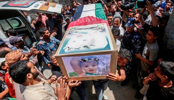 Palestinian mourners carry the bodies of 23-year-old Iyan Khammash and her 18-month-daughter Bayan, during their funeral in Deir Al-Balah in the central Gaza Strip on August 9, 2018, who were killed earlier in an Israeli airstrike. -