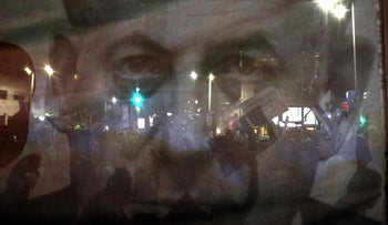 Silhouettes of demonstrators are seen through a giant poster depicting Prime Minister Benjamin Netanyahu at a protest against the nation-state law, Tel Aviv, Israel, August 11, 2018.