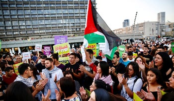Israeli Arabs hold a Palestinian flag during a protest against the nation-state law, Tel Aviv, Israel, August 11, 2018.