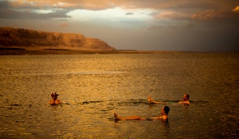 Tourists from Poland float in the Dead Sea during sunset, near Metzoke Dragot in the West Bank, January 25, 2018.