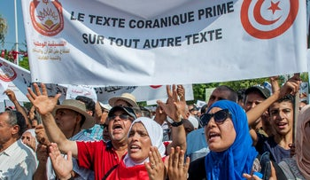 Tunisians demonstrating with a sign that reads: 'Quran before any other text' on August 11, 2018.