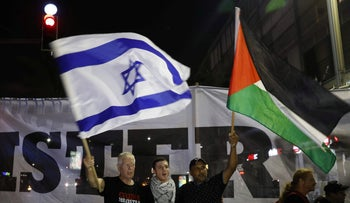 Arab Israelis and their supporters carry a Palestinian and an Israeli flag during a demonstration in Tel Aviv on August 11, 2018.