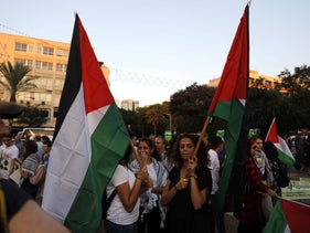 Arab Israelis carry Palestinian flags during a demonstration in Tel Aviv on August 11, 2018.