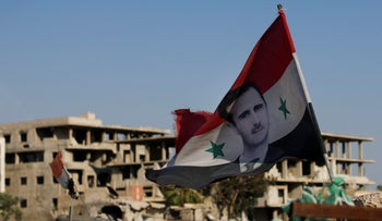 Syrian national flag with the picture of the Syrian President Bashar Assad hangs at an Army check point, in the town of Douma in the eastern Ghouta region, July 15 2018
