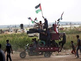 Men wave national flags while riding a motorcycle-taxi, called a Toktok, loaded with tires to be burned during a protest at the Gaza Strip's border with Israel, Friday, Aug. 3, 2018.