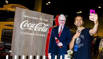 Attendee takes selfie with a cardboard cutout of Warren Buffett, chairman and chief executive officer of Berkshire Hathaway Inc., at the Coca-Cola Co. booth during a shareholders shopping day ahead of the Berkshire Hathaway annual meeting in Omaha, Nebraska, U.S., on Friday, May 4, 2018.