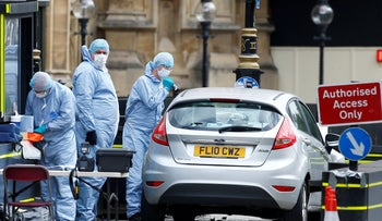 Forensic investigators work at the site after a car crashed outside the Houses of Parliament in Westminster August 14, 2018.