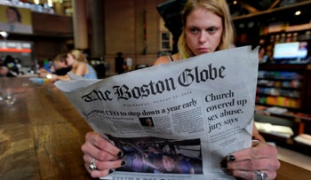 Boston woman Lauren Vowells, 29, reads a copy of the Boston Globe, the newspaper that has organized a push for August 16, 2018 against Trump's 'enemy of the people' attacks on the press.