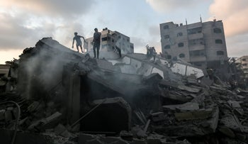 A picture taken on August 9, 2018 shows people inspecting the rubble of a building following an Israeli air strike on Gaza City