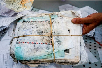Ramadan Ghazawi, a Palestinian official at the central international exchange post office in the West Bank city of Jericho, holds up a stack of letters and postcards, August 14, 2018.