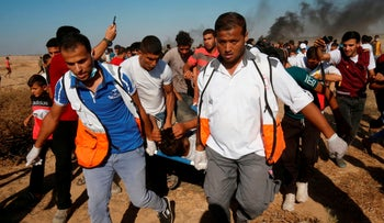 Palestinian paramedics carry an injured protester during demonstrations at the Israel-Gaza border, east of Khan Yunis in the southern Gaza Strip on August 17, 2018