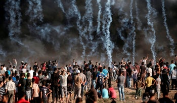 Tear gas canisters, thrown by Israeli forces, fall onto Palestinian protesters during a demonstration along the Israel-Gaza border, east of Gaza City, August 17, 2018.