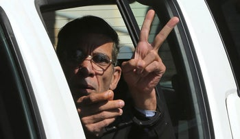 Seif Eddin Mustafa flashes the victory sign from inside a police car after leaving court for a remand hearing in the Cypriot coastal town of Larnaca, March 30, 2016