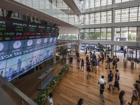 File photo: Visitors stand in front of a stock market ticker screen in the lobby of the Tel Aviv Stock Exchange (TASE) on August 4, 2016.