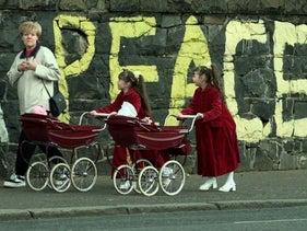 "Mary Dohorty, left, walks past graffiti reading ""Peace"" with her daughters Emma and Amanda, along the Falls Road in a Catholic neighborhood of Belfast, April 11, 1998."