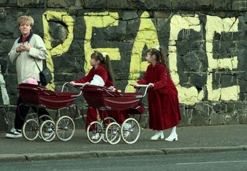"""Mary Dohorty, left, walks past graffiti reading """"Peace"""" with her daughters Emma and Amanda, along the Falls Road in a Catholic neighborhood of Belfast, April 11, 1998."""
