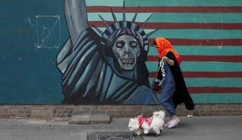 A woman walks her dog past a satirical drawing of Statue of Liberty on the wall of the former U.S. Embassy in Tehran, Iran, Tuesday, May. 8, 2018.