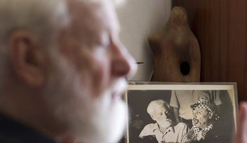In this file photo taken on July 26, 2011, Uri Avnery, Israeli writer and founder of the Gush Shalom peace movement, speaks next to his picture with late Palestinian leader Yasser Arafat