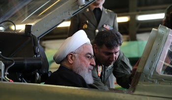 """Picture released by the Iranian Presidency on August 21, 2018, shows President Hassan Rouhani waiving to pilots sitting in the cockpit of the """"Kowsar"""" domestic fighter jet."""