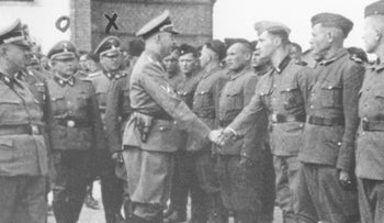 This 1942 photo provided by the the public prosecutor's office in Hamburg shows Heinrich Himmler, center left, shaking hands with new guard recruits at the Trawniki concentration camp in Nazi occupied Poland.