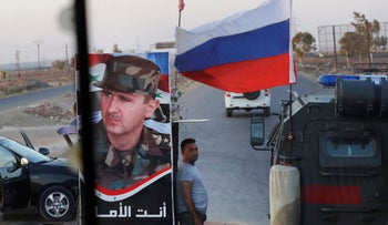Syrian army soldier stands at a checkpoint as Russian military police vehicle passes by, Syria, August 14, 2018.