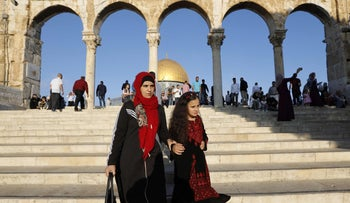 A woman and a child dressed in traditional Palestinian dresses walk near the Dome of the Rock, Jerusalem's Old City, August 21, 2018.