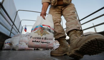 A Russian officer prepares to distribute a food aid for local residents in outskirts of Syrian capital Damascus, Monday, Aug. 13, 2018.