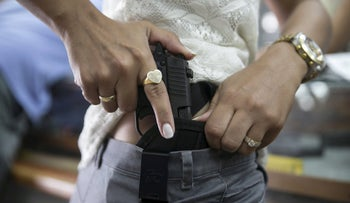 An Israeli woman checks out a new pistol at a gun shop in Tel Aviv October 20, 2015.