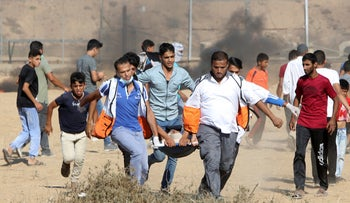 Medics and protesters evacuate a wounded youth near the fence of the Gaza Strip border with Israel, during a protest east of Khan Younis, southern Gaza Strip, Aug. 17, 2018.