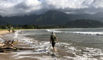 People walk along a calm Hanalei Beach as Hurricane Lane approaches Kauai, Hawaii, U.S., August 22, 2018.