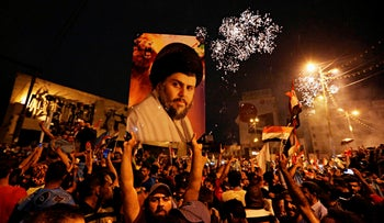 Supporters of Shi'ite cleric Muqtada al-Sadr carry his image as they celebrate in Tahrir Square, Baghdad, Iraq, May 14, 2018.