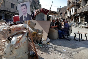 Syrian soldiers man a checkpoint with a picture of President Bashar Assad at the Yarmouk Palestinian refugee camp in Damascus, July 16, 2018.