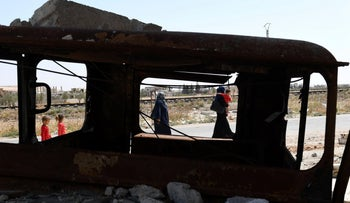 Syrian civilians are seen through a burned vehicle enter the Abu Duhur crossing on the eastern edge of Idlib province on August 20, 2018