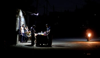 A Palestinian man sells falafel as he uses a battery-powered lamp during a power cut in northern Gaza, August 6, 2018.