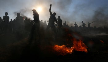 Palestinian protesters hurling stones at Israeli troops during a protest at the Gaza border, August 24, 2018.