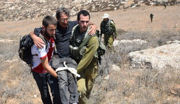 Soldiers evacuating an injured activist after the attack in South Hebron Hills, August 25, 2018.