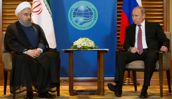 Russian President Vladimir Putin, right, speaks to Iranian President Hassan Rohani during their meeting in Qingdao, China, on June 9, 2018.