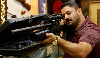 A man checks a weapon before he buys at a weapons shop in Baghdad, Iraq, August 11, 2018.