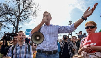 Russian opposition leader Alexei Navalny, center, gestures as he speaks using a loudspeaker at a demonstration against President Vladimir Putin in Pushkin Square in Moscow, Russia.