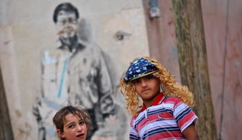 With a painting depicting the late Palestinian poet Mahmoud Darwish in the background, Palestinian children play in an alley in the West Bank refugee camp of Al-Amari in Ramallah, May 27, 2009.