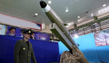 Defense Minister Gen. Amir Hatami walks past the missile Fateh-e Mobin, or Bright Conqueror, during inauguration of its production line at an undisclosed location, Iran, on August 13, 2018.