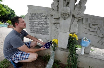 English teacher Derek Davis from the U.S. places a U.S. flag and flowers in memory of the late U.S. Senator John McCain (R-AZ) at the McCain Memorial in Hanoi, Vietnam August 26, 2018.